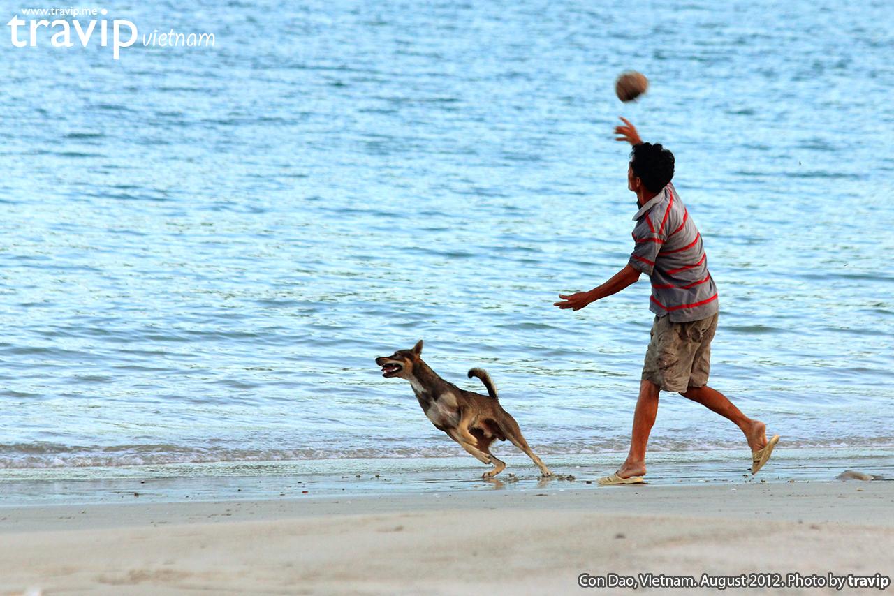 Người dân Côn Đảo nô đùa cùng chú chó trên bãi biển lúc hoàng hôn.